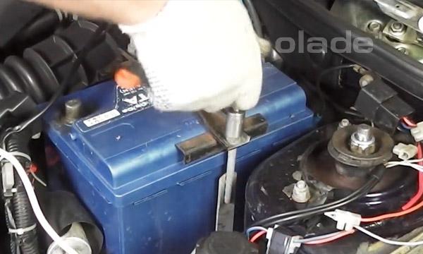 Открутить гайки крепления верхней скобы крепления аккумулятора Лады