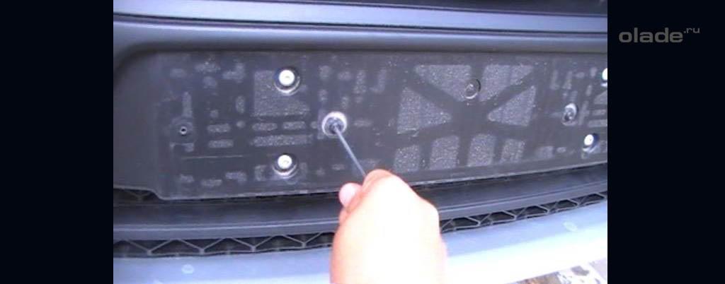 Снятие переднего бампера на Ладе Веста, открутите 2 болта под номерным знаком